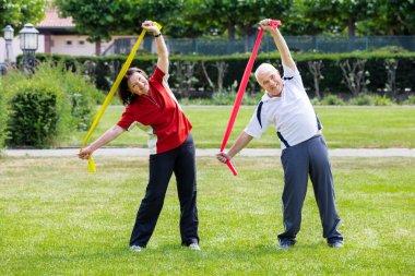 Senior Couple Exercising With Yoga Belts