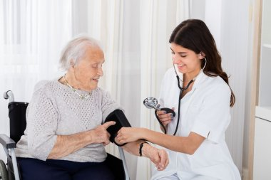 Female Doctor Checking Blood Pressure Of Senior Woman