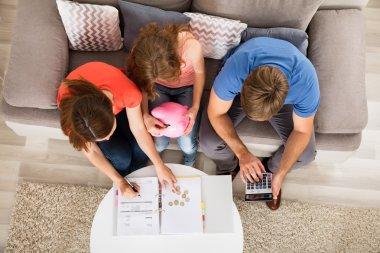 Family Sitting On Sofa Calculating Bill