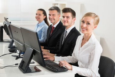 Businesspeople Typing On Desktop Computers