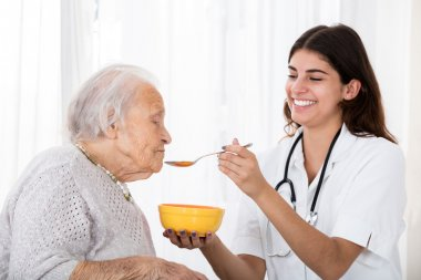 Doctor Feeding Soup To Senior Patient