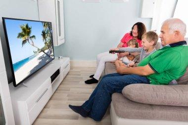 Grandparent And Grandchildren Watching Television