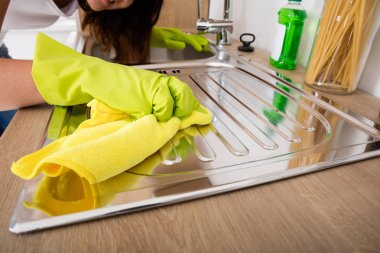 Woman Cleaning Stainless Sink