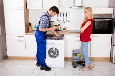 Male Worker Repairing Washer