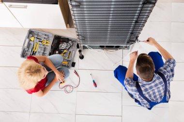 Male Worker Repairing Refrigerator