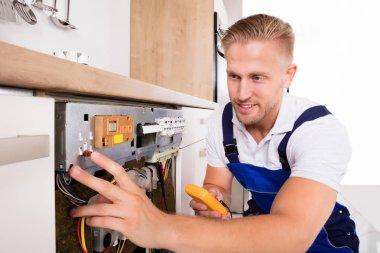Technician Fixing Dishwasher