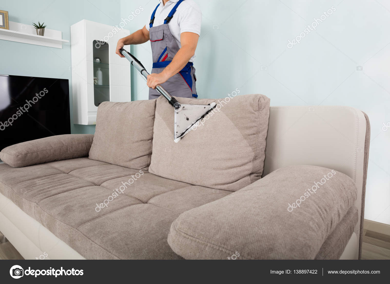 Young Male Worker Cleaning Sofa With Vacuum Cleaner U2014 Photo By AndreyPopov