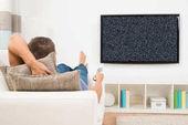 Ember néz televízió távirányítóval