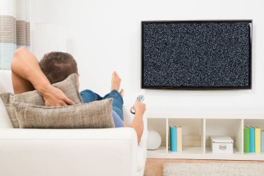 Man With Remote Control Watching Television