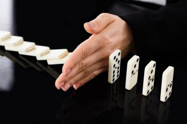 Businesswoman Stopping Dominoes