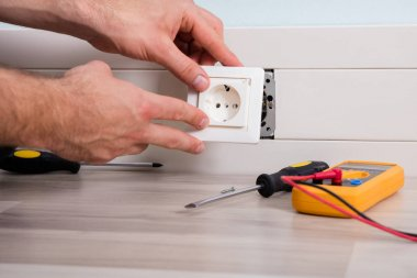 Person Installing Socket On Wall