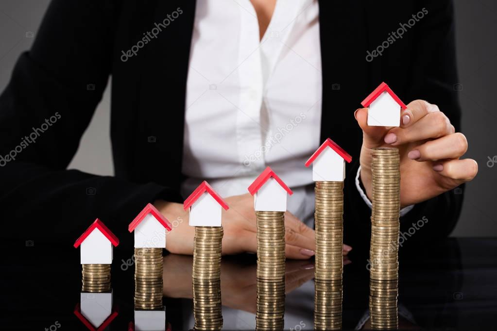 Businesswoman Arranging House Model