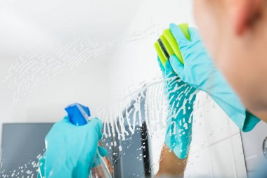 Person Cleaning Mirror