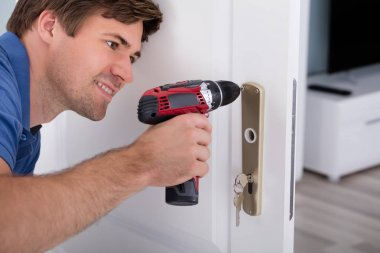 Young Male Installing Door Lock