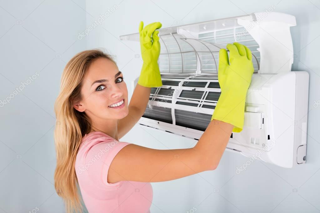 Woman Cleaning Air Conditioner