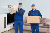 Movers Carrying Rolled Carpet
