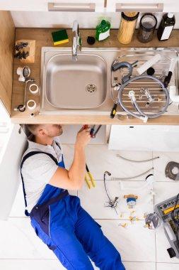 Male Plumber Repairing Sink