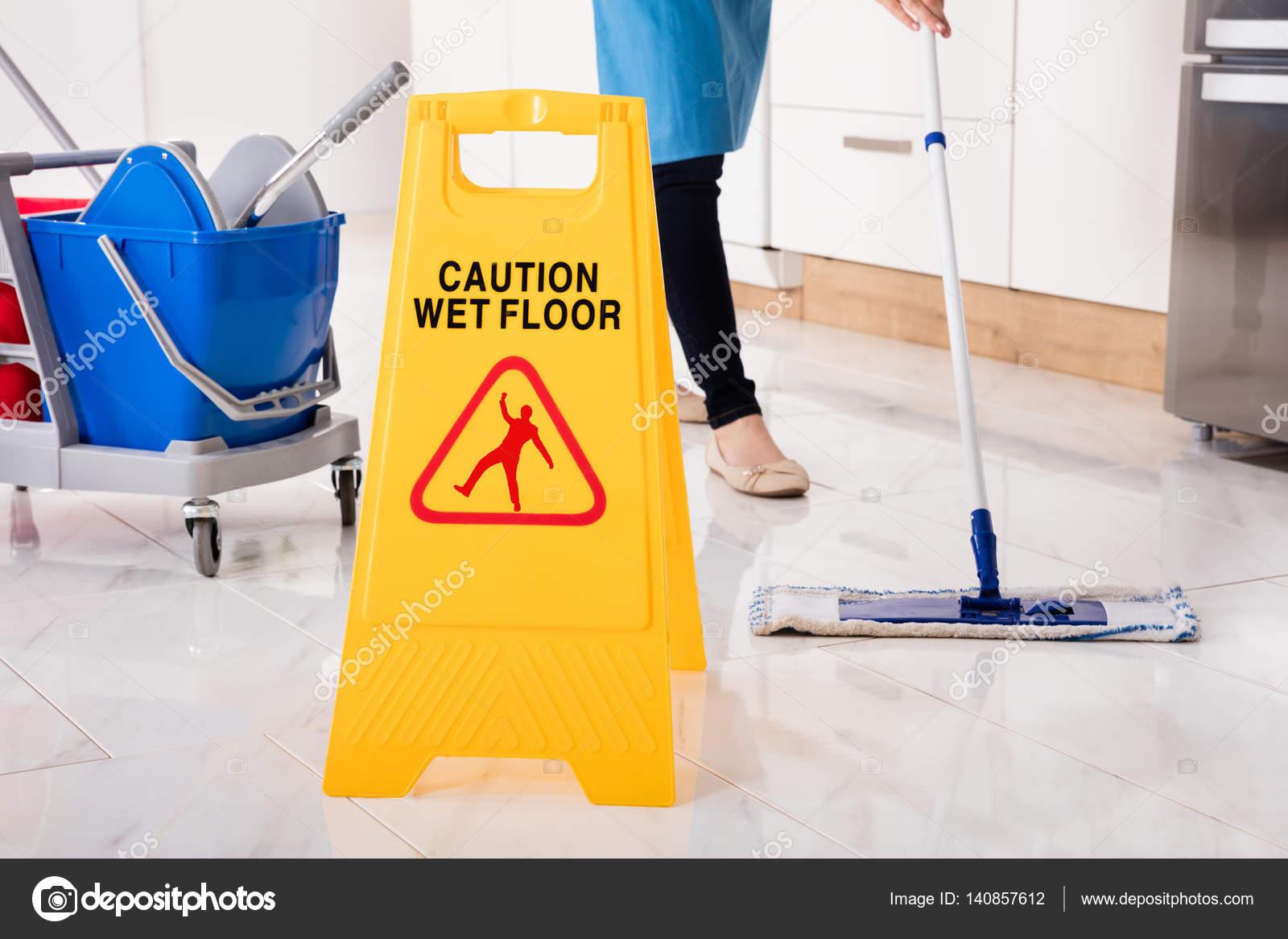 Yellow wet caution sign on wet floor in kitchen stock for Floor banner