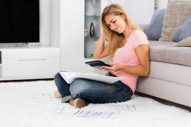 Frustrated Woman Looking At Calculator