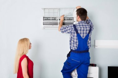 Male Technician Repairing AC