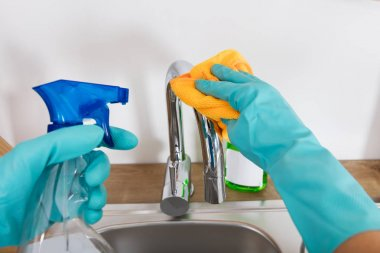 Person Cleaning Sink Tap
