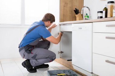 Repairman Fixing Cabinet Hinge