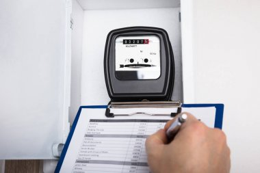 Technician Writing Reading Of Meter