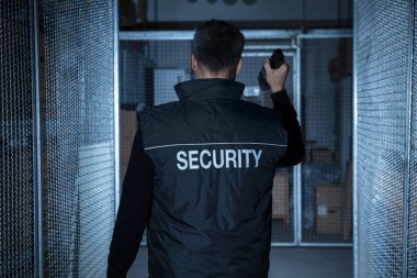 Security Guard Standing In Warehouse