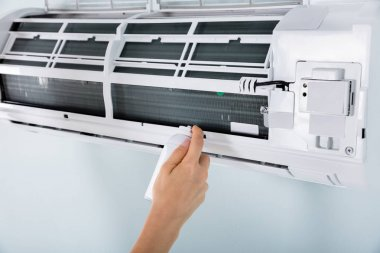 Close-up Of Female Cleaning Air Conditioner