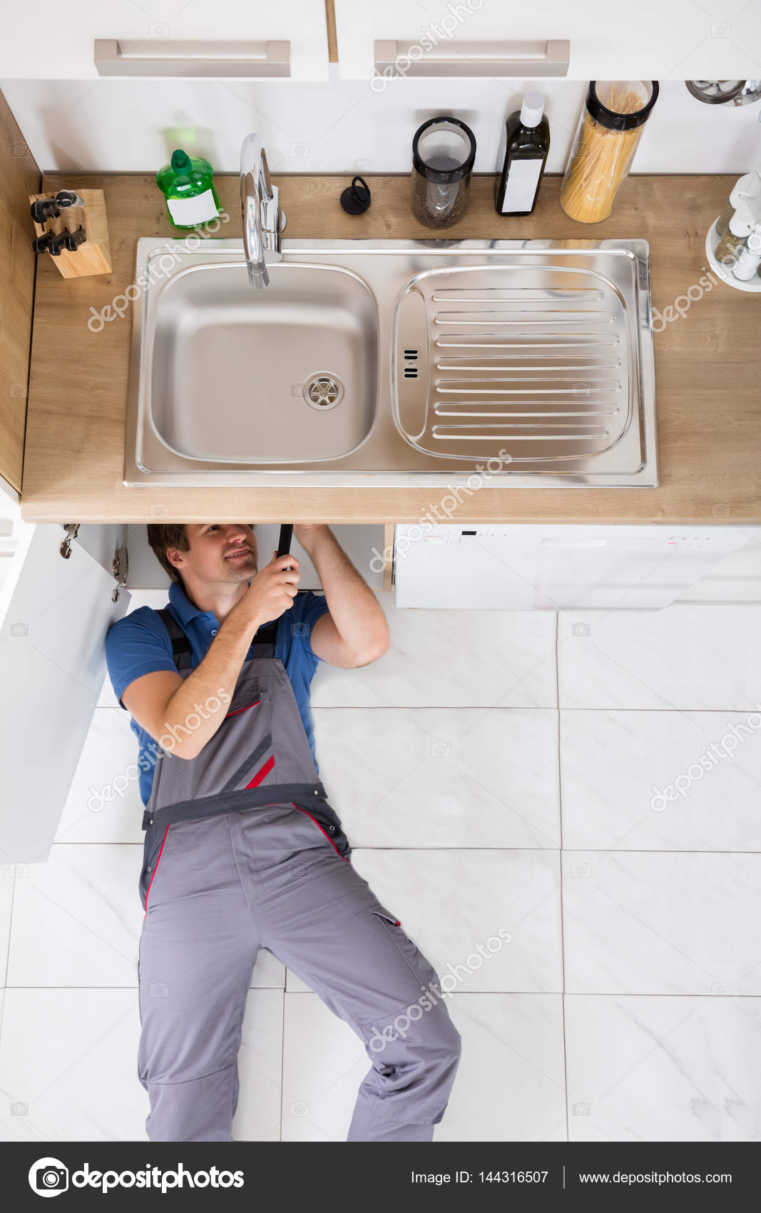 Smiling Plumber Fixing Sink — Stock Photo © AndreyPopov #144316507