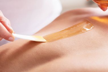 Woman Waxing Man Chest