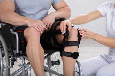 Physiotherapist Fixing Knee Braces