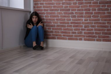 Woman Sitting in Corner