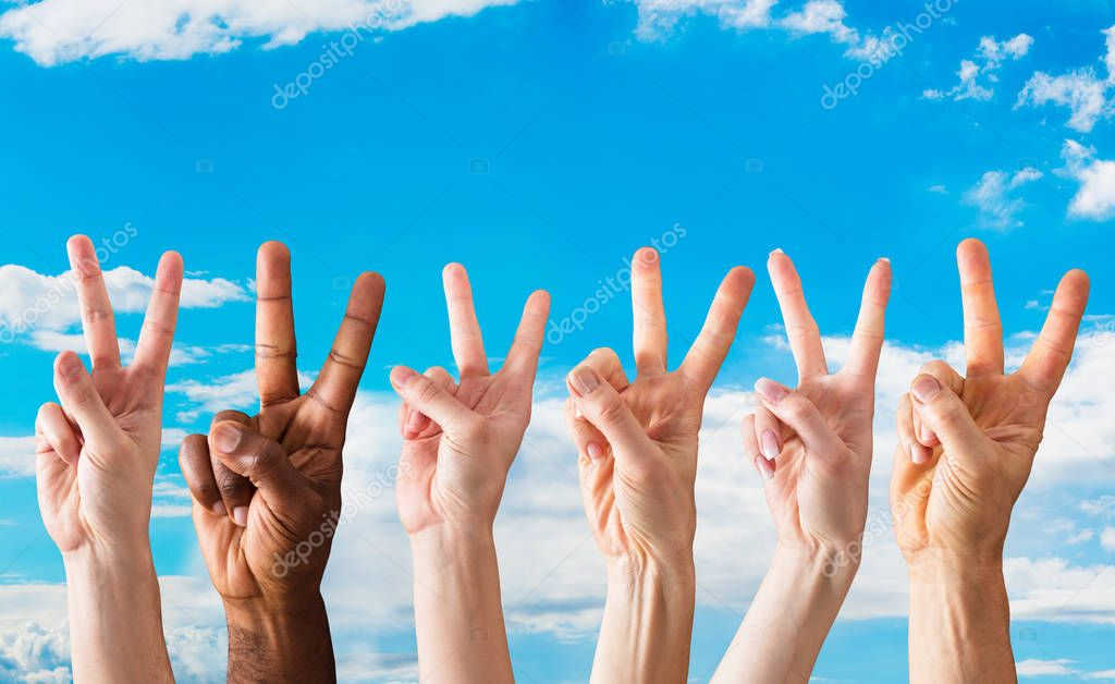 Group Of Hands Showing The Signs Of Peace Against The Blue Sky