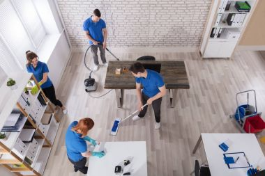 Elevated View Of Janitors In Uniform Cleaning The Modern Office With Cleaning Equipments