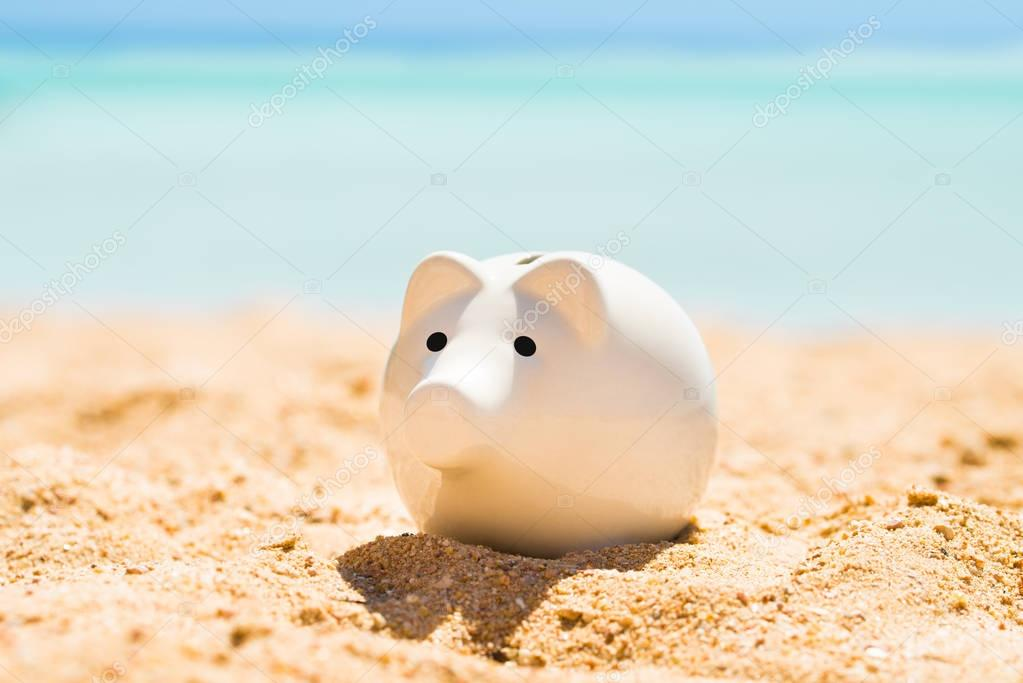 A White Piggy Bank On Sand At Beach In Summer