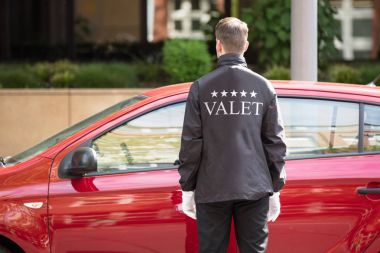 Young Male Valet Opening Car