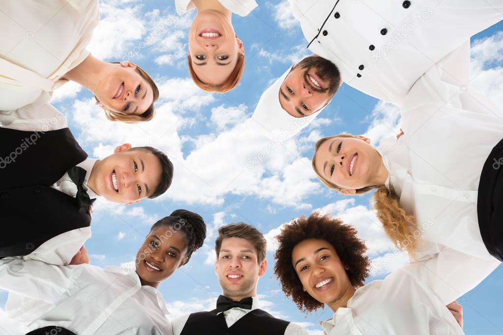 Smiling Restaurant Staff Forming Huddle