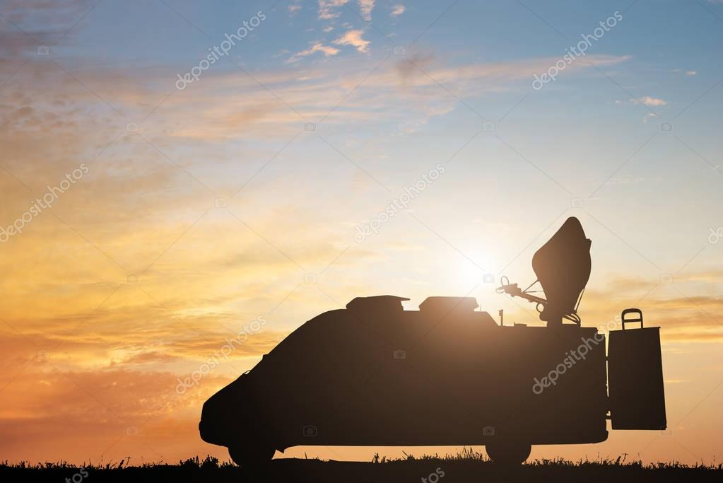 Silhouette Of TV News Truck Against Dramatic Sky At Sunset