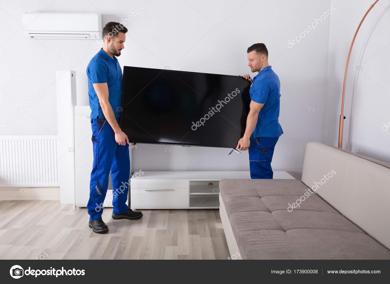 Zwei Junge Männliche Umzugsunternehmen In Uniform Fernseher Im Wohnzimmer  Platzieren U2014 Foto Von AndreyPopov