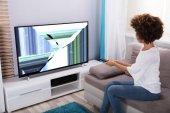 Fiatal nő ül a kanapén közelében televíziós torz képernyő