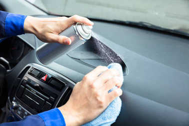 Close-up Of Worker's Hand Cleaning Car Steering Wheel Using Spray Can And Cloth