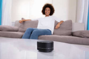 Close-up Of Wireless Speaker In Front Of Woman Sitting On Sofa