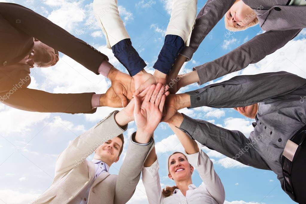 Low Section View Of Businesspeople Stacking Their Hands Against Sky