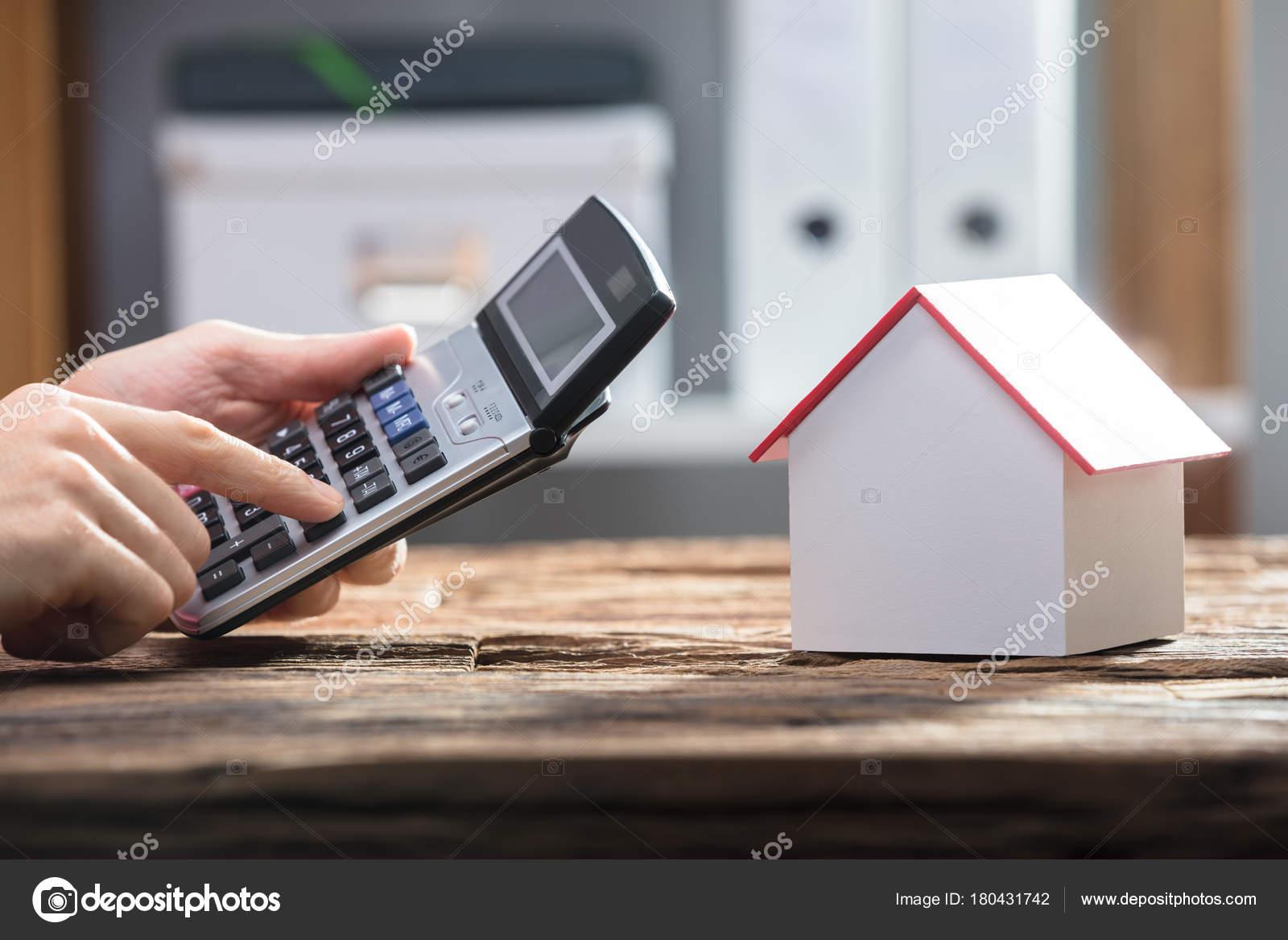 Menschliche Hand Mit Taschenrechner Mit Hausmodell Auf Schreibtisch Aus  Holz U2014 Stockfoto