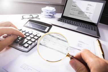 High Angle View Of A Businessperson Analyzing Bill With Magnifying Glass In Office