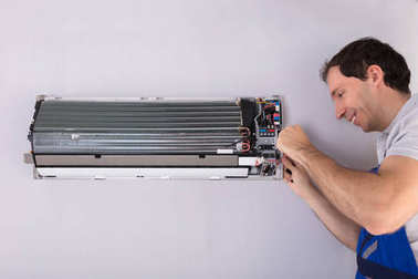 Male Technician Repairing Air Conditioner With Screwdriver