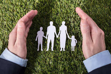 Elevated View Of A Person's Hand Protecting Family Paper Cut Out On Green Grass