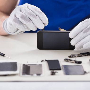 Close-up Of A Human Hand Repairing Smartphone With Screwdriver