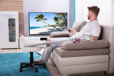 Man With Broken Leg Sitting On Sofa Watching Television At Home